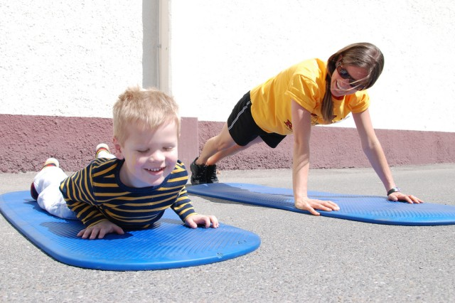 Caitlin Smith, CYS Services Acting Director of Sports and Fitness exercises with an unidentified boy during April's Month of the Military Child in Stuttgard.