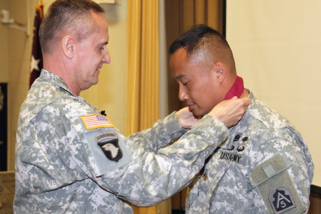 FORT SAM HOUSTON, Texas -- Maj. John Nguyen receives the Order of Military Medical Merit from Brig. Gen. Dennis Doyle during Doyle's visit to speak with medical service officers May 1 at the Army Medical Department Center and School's Blesse Auditorium. Nguyen, the medical plans and operations officer for U.S. Army North (Fifth Army), was nominated for admission into the order because of his commitment to the betterment of Army medicine, dedicated application of his talents, efforts and spirit and his selfless service to the Nation. Doyle is the chief of the Army Medical Service Corps. The Order of Military Merit is a unique, private organization founded in April 1982 to recognize excellence and promote fellowship and esprit de corps among AMEDD personnel.