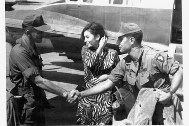 "1st Lt. Stephen ""Steve"" Patterson (right) shakes hands with the commander of 1st Brigade Combat Team, 101st Airborne Division at Camp Eagle in South Vietnam.  Between the two men is Linda Artavia-Patterson during her visit to A Company, 1st Battalion, 327th Infantry Regiment in December, 1968.  This is where their love story began."