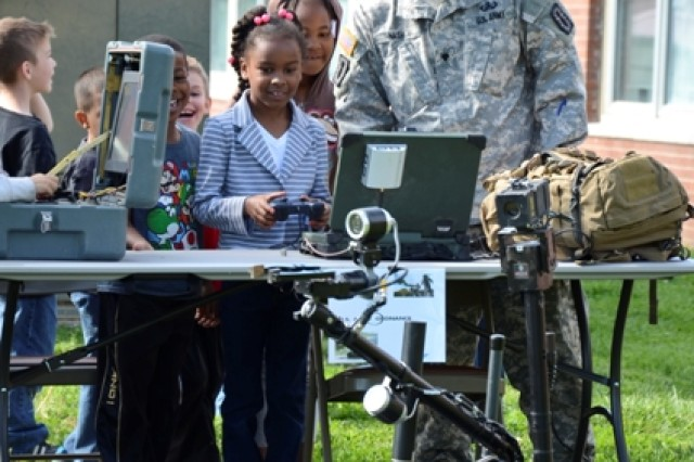 First grader Clara Gaskins, 6, operates a TALON robot as Spc. Brian Nash, 49th Ordnance Company, supervises at the career fair May 2. The station gave students an opportunity to control the robots via remote, as well as learn about how they are used in both military and civilian occupations.