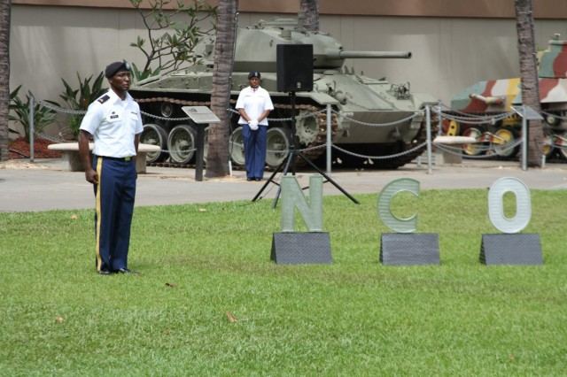 A noncommissioned officer representing the rank of sergeant stands next to the NCO sign after explaining his role in the NCO support channel during an NCO Induction Ceremony, May 16, hosted by the 8th Special Troops Battalion, 8th Theater Sustainment Command at historic Fort DeRussy Army Museum, Honolulu, Hawaii.