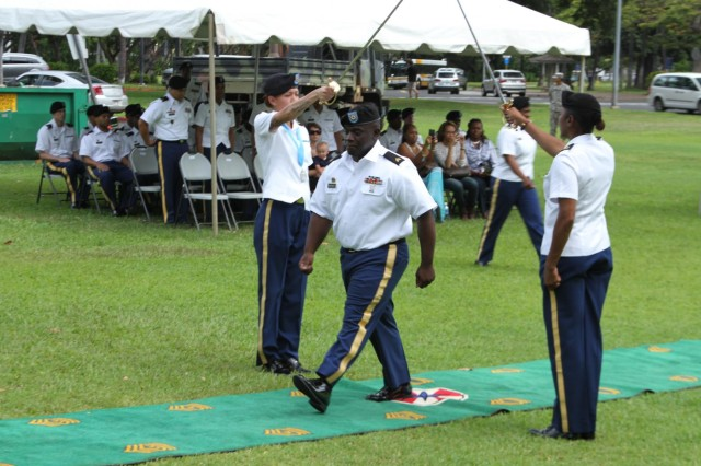One of 24 newly inducted noncommissioned officers pass beneath the NCO swords that symbolizes the transition from Soldier to NCO during an NCO Induction Ceremony, May 16, hosted by the 8th Special Troop Battalion, 8th Theater Sustainment Command, at historic Fort DeRussy Army Museum, Honolulu, Hawaii.