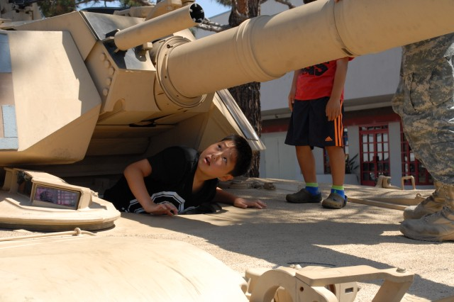 Eric Hwang looks out of the drivers hatch on a M1 Abrams Main Battle Tank, at the display area for Torrance Armed Forces Days