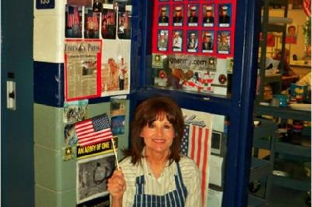 Jolee Mockler, an art teacher at Reedsburg Area High School in Reedsburg, Wis., sits in front of her 'Wall of Heroes' that showcases service members who send her photos. The wall started after Sept. 11, 2001, when some of her former students joined the military after the 9/11 terrorist attacks.
