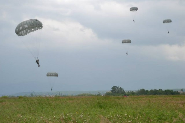 DAKOVICA AIRFIELD, Kosovo -- U.S. Army paratroopers with 2nd Squadron, 38th Cavalry Regiment descend to the ground after parachuting 1,000 feet from a U.S. Air Force C-130, May 12, as part of the squadron's ongoing efforts to maintain airborne proficiency in unfamiliar areas like Kosovo. This is the squadron's second airborne operation in Kosovo, and the first to use the Army's MC-6 parachute system.