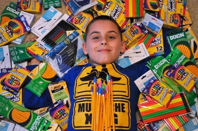 """COPPERAS COVE, Texas -- Matthew Northrop, 8, surrounds himself with donated pens, pencils, crayons and colored pencils for Kosovo students as part of his unique fundraising drive, """"Helping Kids in Kosovo Write Their Future."""" Northrop raised over $500 and enough supplies to fill 12 large boxes. The supplies will be sent to rural schools in Kosovo."""