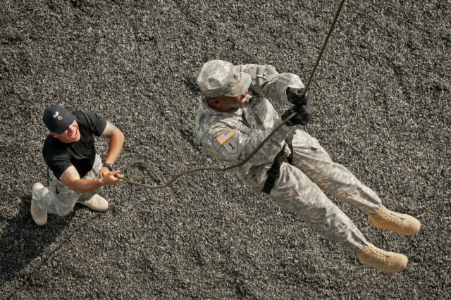 U.S. Army Sgt. 1st Class Jeremy Jackson, a course chief at the Fort Hood Air Assault School from New Orleans, finishes the 50-foot rappel out of the FHAAS rappel tower as Staff Sgt. Kevin Serna, of San Marcos, Texas, anchors the rope, May 7, 2014. Air Assault School qualifies Soldiers to conduct airmobile and air assault helicopter operations, to include aircraft orientation, sling load operations, proper rappelling techniques and fast-rope techniques. The school itself is 10 days of rigorous, fast paced training. The high standards of the school require the student to take part in a 12-mile march with rucksack in under three hours on the morning of graduation to be awarded their wings. Iterations of the FHAAS begin with 132 students, and end with an average of 80 graduates. (U.S. Army photograph by Sgt. Ken Scar, 7th Mobile Public Affairs Detachment)