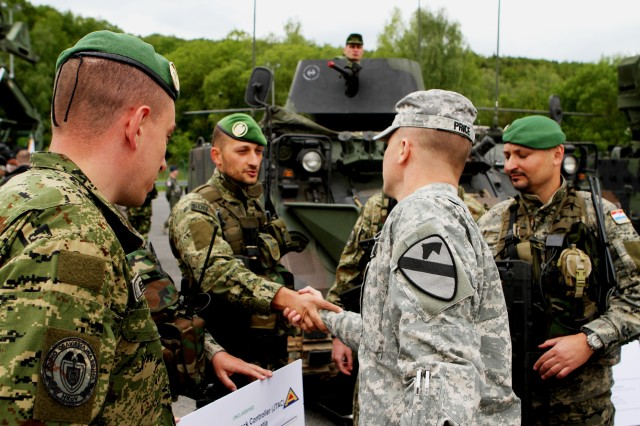 Lt. Col Carter Price, commander of 2nd Battalion, 5th Cavalry Regiment, 1st Brigade Combat Team, 1st Cavalry Division, shakes hands with Croatian Soldiers during a capabilities day presentation prior to the start of Combined Resolve II. Secretary of the Army John M. McHugh focused on the implementation of U.S. Army Europe's regionally aligned forces concept while observing Soldiers and NATO and European partners at exercise Combined Resolve II (U.S. Army photo by Capt. John Farmer, 1st BCT, 1st CD Public Affairs).