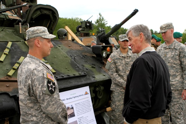 Secretary of the Army, John McHugh, right, talks about Bradleys with Staff Sgt. Carl King, left, a Bradley Fighting Vehicle Commander with Headquarters and Headquarters Company, 2nd Battalion, 5th Cavalry Regiment, 1st Brigade Combat Team, 1st Cavalry Division at Hohenfels Army base during a capabilities day presentation prior to the start of Combined Resolve II. Secretary of the Army John M. McHugh focused on the implementation of U.S. Army Europe's regionally aligned forces concept while observing Soldiers and NATO and European partners at exercise Combined Resolve II (U.S. Army photo by Capt. John Farmer, 1st BCT, 1st CD Public Affairs).
