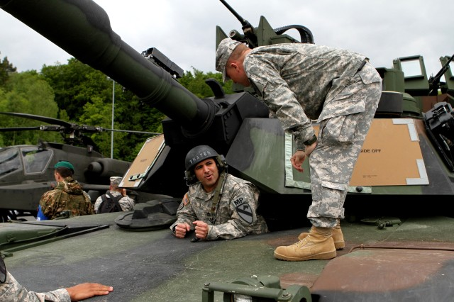 Lt. Col Carter Price, right, commander of 2nd Battalion, 5th Cavalry Regiment, 1st Brigade Combat Team, 1st Cavalry Division coaches Sgt. 1st Class Ivan Alvira, the 1st BCT Provost Marshall noncommissioned officer in charge on how to properly enter the driver's hole of an Abrams tank at Hohenfels Army base during a capabilities day presentation prior to the start of Combined Resolve II. Secretary of the Army John M. McHugh focused on the implementation of U.S. Army Europe's regionally aligned forces concept while observing Soldiers and NATO and European partners at exercise Combined Resolve II (U.S. Army photo by Capt. John Farmer, 1st BCT, 1st CD Public Affairs).