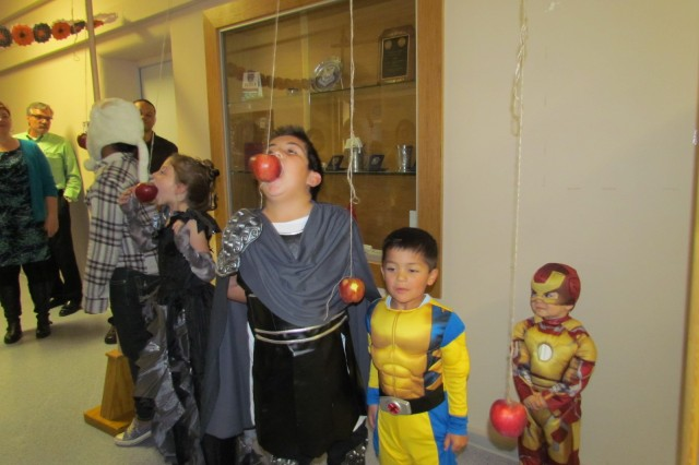 Children enjoy apple bobbing games during a 409th Contracting Support Brigade Family Readiness Group Halloween-themed meeting in Kaiserslautern, Germany.