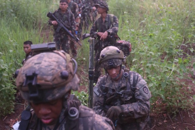 Philippine soldiers from 20th Infantry Battalion, 8th Infantry Division, and U.S. Soldiers from Comanche Troop, 3rd Squadron, 4th Cavalry Regiment, 25th Infantry Division, conduct a nine-hour hike through mountainous jungle terrain to reach their objective, during a battalion field training exercise as the culminating event for Balikatan 2014, May 15, 2014, at Fort Ramon Magsaysay, Philippines.