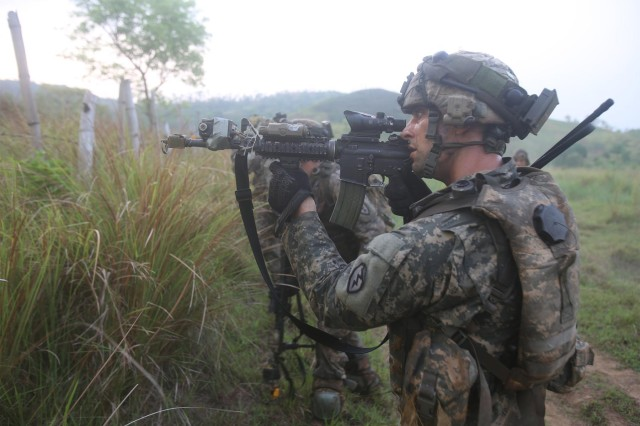 Sgt. Justin M. Cormany, platoon sergeant, Comanche Troop, 3rd Squadron, 4th Cavalry Regiment, 25th Infantry Division, secures the area after neutralizing enemies during a battalion field training exercise as the culminating event for Balikatan 2014, May 15, 2014, at Fort Ramon Magsaysay, Philippines.