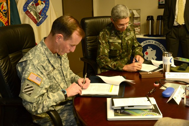 Maj. Gen. Joseph P. DiSalvo (left), the commanding general of U.S. Army South, and Maj. Gen. Joarez Alves Pereira Jr., the head of the Brazilian delegation, sign a memorandum of understanding outlining engagements between the U.S. and Brazilian armies in 2015 during the U.S. Army/Brazil Staff Talks at the Army South headquarters May 14.
