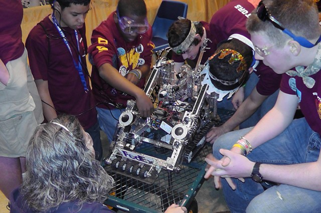 From left, Ricardo Cosme, Devante Monley, Garrett Juliar, Reggie Munguia and Elijah Schwartz work on repairing their robot at the world championship robotics competition in St. Louis, Missouri in April.