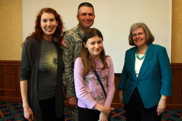 Holly Petraeus, assistant director of the Consumer Financial Protection Bureau Service Member Affairs, meets with Staff Sgt. Robert Mathis, 18th Military Police Brigade, and his family, following a town hall meeting at the Armstrong's Club in Kaiserslautern, Germany, May 16. CFPB is an independent federal agency that ensures financial institutions support consumers honestly and enforces 18 different federal consumer financial laws.