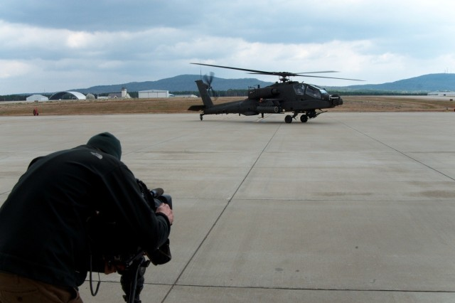 A Fox News Channel photographer records as Chief Warrant Officer 5 Paul Steele and Chief Warrant Officer 4 Michael Kennedy takeoff in an AH-64E to begin their mission during a recent media visit.