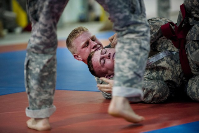 Spc. Jessie Clements (top), of Lafayette, Ga., with the 390th Engineer Company, grapples with Spc. Cody Blunt, of Sauquoit, N.Y., with the 497th Engineer Battalion, at the modern Army combatives tournament during the combined Regional Best Warrior competition hosted by the 412th and 416th Theater Engineer Commands at Fort McCoy, Wis., April 30. (U.S. Army photo by Sgt. 1st Class Michel Sauret)