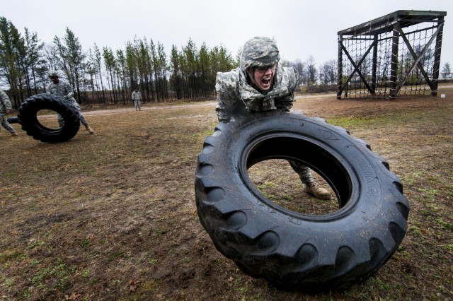 Spc. Logan Lariscy with the 375th Engineer Company flips a tire during a conditioning course as part of the 412th and 416th Theater Engineer Commands' combined regional Best Warrior competition held at Fort McCoy, Wis., April 29. (U.S. Army photo by Sgt. 1st Class Michel Sauret)
