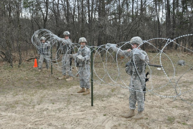 Spc. Antonio Munoz, Kansas City, Mo., Spc. Cary Goggins, Fayetteville, Ark., Staff Sgt. Billy Daffron, St. Joseph, Mo., and Spc. Kyle Malone, Kansas City, Mo., with the 348th Engineer Company install a 30-meter wire obstacle made of concertina wire, barbed wire, and baling wire to secure a compound from enemy incursion during the 2014 Sapper Stakes that pit engineer unit teams against each other as they vie to win the inaugural competition.