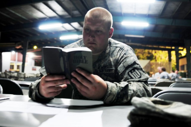 Pfc. Josiah Williams, chaplain's assistant of the 372nd Engineer Brigade of Minnesota, reads along during a religious service offered by Lt. Col. John Meyer, chaplain of the 372nd Engineer Brigade, during Beyond the Horizon 2014 - Guatemala, May 11, 2014.  (U.S. Army National Guard Photo by Pfc. Haley E. Haile/Released)