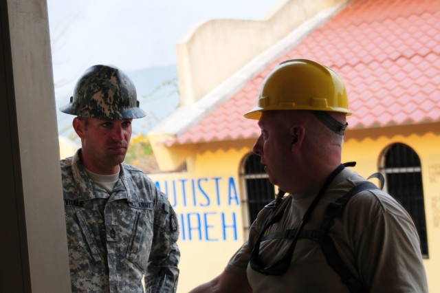 Lt. Col. John Meyer (yellow hard hat), chaplain of the 372nd Engineer Brigade in Minnesota, discusses the construction of a two-room school building with Sgt. 1st Class Matthew Vitale, the site noncommissioned officer in charge at Conevisa from the 35th Engineer Brigade of Missouri, during Beyond the Horizon 2014 - Guatemala, May 7, 2014.  Beyond the Horizon is a joint partnership between the United States and Central and South America and the Caribbean to bring medical, dental, and engineering programs to the local communities. (U.S. Army National Guard Photo by Pfc. Haley E. Haile/Released)