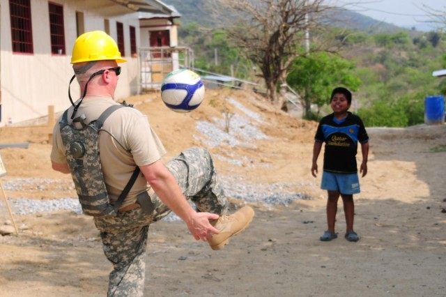 Chaplain Lt. Col. John Meyer, chaplain of the 372nd Engineer Brigade of Minnesota, plays with one of the local children at the Conevisa site during Beyond the Horizon 2014 - Guatemala, May 7, 2014. Beyond the Horizon is a joint partnership between the United States and Central and South America and the Caribbean to bring medical, dental, and engineering programs to the local communities. (U.S. Army National Guard Photo by Pfc. Haley E. Haile/Released)