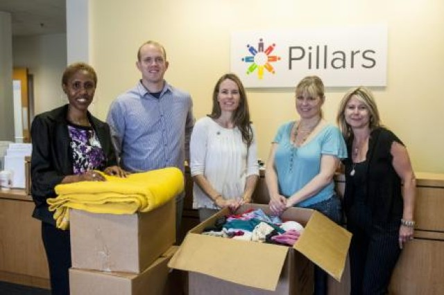 Representatives from the 416th Theater Engineer Command and the Pillars community service agency stand together with boxes full of donated clothes intended for sexual assault victims at the Pillars office in Hickory Hills, Ill., May 19. From left: Camille Kent, of Lisle, Ill., the victims advocate for the 416th TEC; Andrew Jones, the sexual assault response coordinator for the 416th TEC, and resident of Plainfield, Ill.; Katheryn Smith, of Westchester, Ill., volunteer coordinator and community relations specialist for Pillars; Christy Bowes, of Chicago, prevention educator and advocate for Pillars; and Patty Murphy, of Oak Lawn, Ill., the director of advocacy for Pillars. The clothes were donated by Reserve Soldiers as part of a clothing drive initiative during April, known nationally as Sexual Assault Awareness Month. (U.S. Army photo by Sgt. 1st Class Michel Sauret)