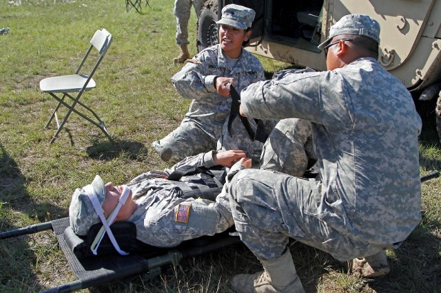 """Spc. Pamela Sandoval (center) and Spc. Keala Mamala (right), both combat medics assigned to the 115th Brigade Support Battalion """"Muleskinner,"""" 1st Brigade Combat Team """"Ironhorse,"""" 1st Cavalry Division, use a Kendrick Extraction Device to demonstrate how to move a casualty, played by Pfc. Cord Shotton, an infantryman assigned to the 2nd Battalion """"Stallion,"""" 8th Cavalry Regiment of the Ironhorse Brigade, during training for the Expert Field Medical Badge May 14 at Fort Hood, Texas. More than 200 Soldiers across the post participated as cadre, candidates and support during EFMB training and testing. (U.S. Army photo by Spc. Paige Behringer, 1BCT PAO, 1st Cav. Div.)"""