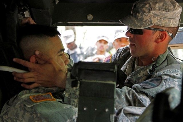 """Spc. Joseph Giardina, a Phoenix native and combat medic assigned to Troop A, 1st Squadron, 7th Cavalry Regiment """"Garryowen,"""" 1st Brigade Combat Team """"Ironhorse,"""" 1st Cavalry Division, applies a Kendrick Extraction Device to a simulated casualty, Spc. Reymar Duza, a Las Vegas native and cannon crewmember assigned to the 1st Battalion """"Dragon,"""" 82nd Field Artillery Regiment, Ironhorse Brigade, during training for the Expert Field Medical Badge May 14 at Fort Hood, Texas. The 10-day exercise prepares candidates for the testing phase with a training portion in which Soldiers are shown EFMB tasks and given time to study and practice. (U.S. Army photo by Spc. Paige Behringer, 1BCT PAO, 1st Cav. Div.)"""