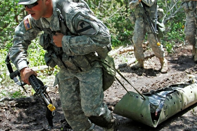 "Spc. Joseph Giardina, a Phoenix native and combat medic assigned to Troop A, 1st Squadron, 7th Cavalry Regiment ""Garryowen,"" 1st Brigade Combat Team ""Ironhorse,"" 1st Cavalry Division, pulls a simulated casualty using a Skedco stretcher during training for the Expert Field Medical Badge May 14 at Fort Hood, Texas. The EFMB is a non-combat badge awarded to medical Soldiers who complete a series of written and performance tests. (U.S. Army photo by Spc. Paige Behringer, 1BCT PAO, 1st Cav. Div.)"