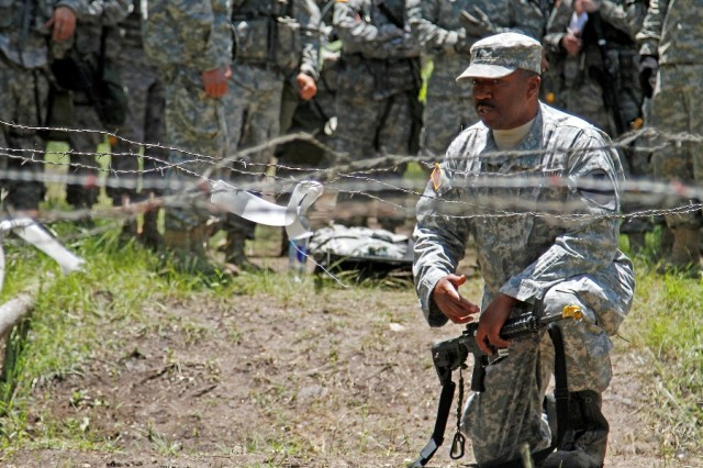 """Sgt. Paulus Smallwood, a Lexington Park, Maryland, native and radiology specialist assigned to the 115th Brigade Support Battalion """"Muleskinner,"""" 1st Brigade Combat Team """"Ironhorse,"""" 1st Cavalry Division, gestures to a barbed-wire obstacle while describing tasks in a Combat Trauma Lane during training for the Expert Field Medical Badge May 14 at Fort Hood, Texas. As a grader, Smallwood not only evaluates each candidate's performance during testing, but he also teaches candidates how to properly execute each task, ensuring they are given the knowledge necessary to succeed. (U.S. Army photo by Spc. Paige Behringer, 1BCT PAO, 1st Cav. Div.)"""