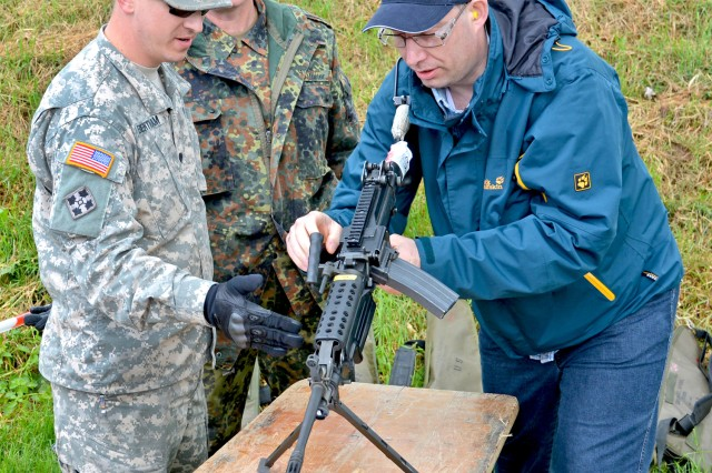 Spc. Justin Bentham, 1st Battalion, 214th Aviation Regiment, instructs Bundeswehr Reserve Feldwebel (Sgt.) Andreas Bachmeier on the use of the M249 Squad Automatic Weapon at the Monte Kali International Shooting Competition, in Wackernheim, Germany.