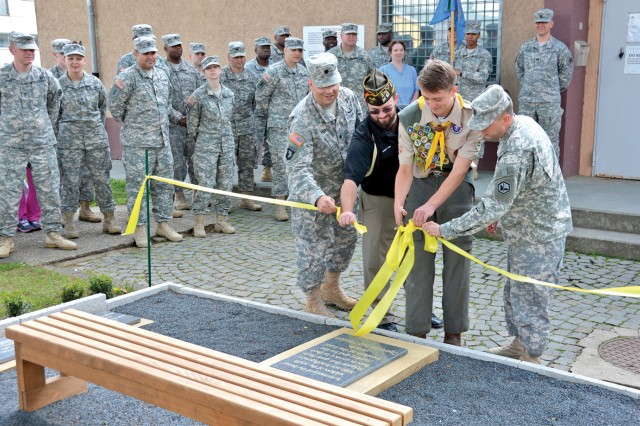 Brayden Love cuts the ribbon to rededicate the 205th Military Intelligence Brigade Memorial located outside the 2nd MI Battalion Headquarters on Wiesbaden's Clay Kaserne. The memorial pays tribute to Soldiers killed in Iraq during Operation Iraqi Freedom.