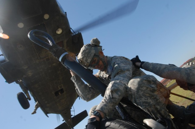 Sgt. Timothy Harris, a signal support systems specialist with Battery B, 1st Battalion, 76th Field Artillery Regiment, 4th Infantry Brigade Combat Team, 3rd Infantry Division, prepares to sling load an M119A2 howitzer to a UH-60L Black Hawk helicopter during air assault training on Fort Stewart, Ga., May 16, 2014. (Photo by Sgt. Joshua Laidacker, 4 IBCT, 3 ID, Public Affairs)