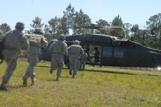 Soldiers of Battery B, 1st Battalion, 76th Field Artillery Regiment, 4th Infantry Brigade Combat Team, 3rd Infantry Division, rush into a UH-60L Black Hawk helicopter during air assault training conducted on Fort Stewart, Ga., May 16, 2014. The soldiers conducted a mock two-gun raid to increase proficiency and to train for an upcoming mission to support the U.S. Military Academy at West Point, N.Y. (Photo by Sgt. Joshua Laidacker, 4 IBCT, 3 ID, Public Affairs)