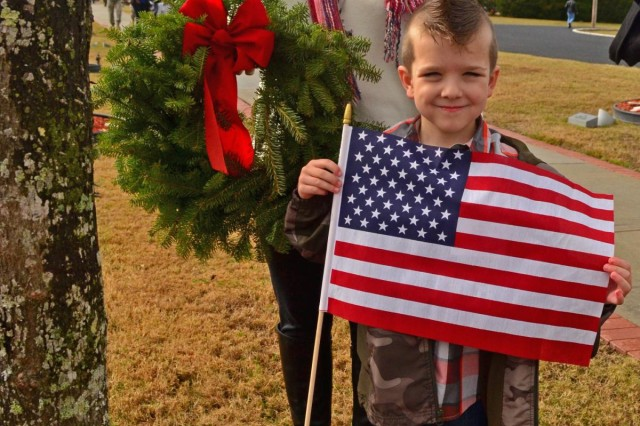 Kimberly Giles, mother of fallen Soldier Pfc. Landon Giles, stands with her grandson, Azrael Bradford, 6, at Pfc. Giles' tree, number 61, at the Fort Stewart Warriors Walk, Dec. 14, 2013. Kimberly attended the wreath laying ceremony and hung ornaments on her son's tree. Giles was killed in action February 26, 2005, while on patrol in Abertha, Iraq. He was an indirect fire infantryman assigned to the 6th Squadron, 8th Cavalry Regiment, 4th Brigade Combat Team, 3rd Infantry Division. Giles had turned 19 three weeks before his death.