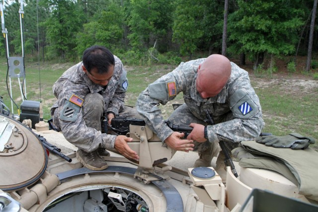 Sgt. Kevin Luu (left), a gunner from Tioga, N.Y., and Spc. Benjamin D. Whiteman, a loader from Townsend, Del., work on a weapon atop a tank, May 12, during the grueling, weeklong 2014 Sullivan Cup Best Tank Crew Competition. Luu and Whiteman were part of the four-man team from Company C, 2nd Battalion, 3rd Armored Brigade Combat Team, 3rd Infantry Division, who won this year's Sullivan Cup Best Tank Crew.