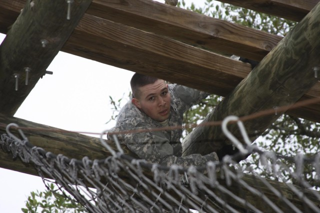 Cpl. Ryan Perea, U.S. Army Garrison Fort Bragg, pulls himself across a beam, navigating through the IMCOM Best Warrior obstacle course May 6 at Joint Base San Antonio-Camp Bullis. (U.S. Army photo by Amanda Kraus Rodriguez)
