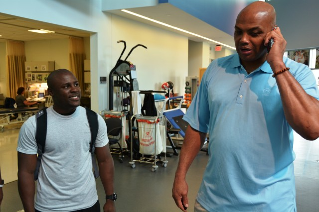 "Airman Basic Michael Thomas looks on as ""Sir Charles"" Barkley, retired National Basketball Association player and current sports commentator, surprises Thomas' wife, Felicia with a phone call during his visit at the Center for the Intrepid on May 20. Barkley, currently in San Antonio for the NBA playoffs, visited with wounded service members and staff at the CFI and made a surprise appearance to San Antonio Military Medical Center to visit inpatients and staff. U.S. Army photo by Robert Shields."