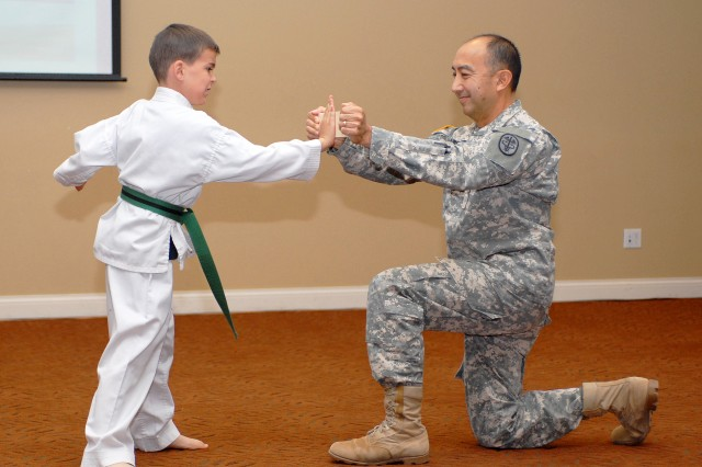 Alexander Ziegler uses his palm to hit a board held by Col. Todd Kimura, commander of United States Army Dental Clinic Command here during a ceremony at Fort Irwin, May 7. Alexander was demonstrating karate skills learned in the program SKIESUnlimited. The program instructs children and youth, ages six weeks to adolescence, in sports, arts, life skills and academics, and provides opportunities to perform their proficiency.