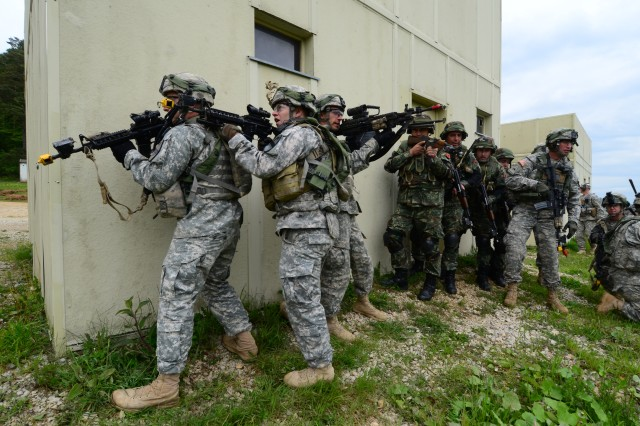 Albanian soldiers and U.S. Soldiers of Bravo Company, 2nd Battalion, 5th Cavalry Regiment, 1st Brigade Combat Team, 1st Cavalry Division, stack on a wall and prepare to assault, during exercise Combined Resolve II at the Joint Multinational Readiness Center in Hohenfels, Germany, May 17, 2014.  Combined Resolve II is a multinational decisive action training environment exercise occurring at the Joint Multinational Training Command's Hohenfels and Grafenwoehr Training Areas that involves more than 4,000 participants from 15 partner nations.  The intent of the exercise is to train and prepare a U.S. led multinational brigade to interoperate with multiple partner nations and execute unified land operations against a complex threat while improving the combat readiness of all participants.