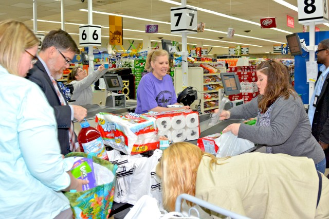 Members of the Wiesbaden Army Community Service help volunteer Gina Twyman tally up and pack her shopping spree haul.