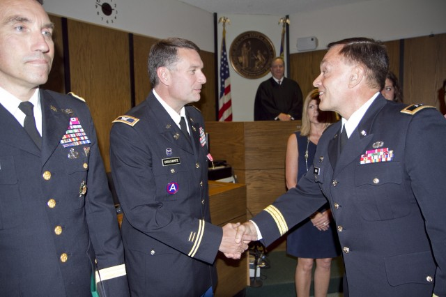 Col. Joseph Crosswhite shakes hands with Maj. Gen. Gill Beck, commanding general of the 81st Regional Support Command, just after the presentation ceremony where he received the Bronze Star Medal at the Hall of Justice in Statesville, N.C., on May 17. Crosswhite served a tour in Afghanistan as an adviser to Afghan prosecutors and judges. Crosshwhite served as the staff judge advocate for the 81st prior to his deployment and is currently the chief of International and Operational Law at Army Forces Command at Fort Bragg, N.C. To Crosswhite's left is retired Maj. Gen. James B. Mallory III, also an attorney in Statesville.