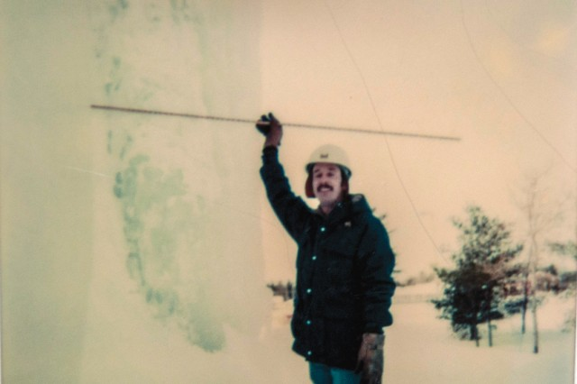 """A photo taken in 1980 shows Corriveau measuring ice as much as three feet thick accumulating on the sides of Building 2300 on South Post. Because """"scuppers"""" in the original roof construction created massive icicles that were damaging the building's masonry block, Corriveau was a part of the engineering team that redesigned the roof's drainage system through heated pipes internally instead of on the perimeters."""