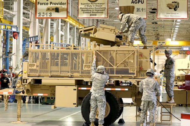 Soldiers from Echo Battery, Third Battalion, Fourth Air Defense Artillery Regiment at Fort Bragg, N.C. emplace the Family Medium Tactical Vehicle based AN/MPQ-64A3 Sentinel Radar in the maintenance facility during the rollout ceremony.