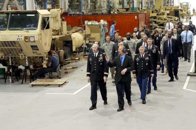 Dale McClanahan, chief, ground equipment division provides a tour of the maintenance facility for Brig. Gen. L. Neil Thurgood and other attendees after the Sentinel A3 Family of Medium Tactical Vehicles rollout ceremony.