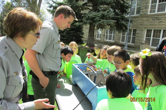 """TRINIDAD, COLO., -- Karen Downey, John Martin Reservoir operations manager, and Nicholas Bailey, park ranger, help students learn about dams at the Albuquerque District's """"Dam Building 101"""" station at the Trinidad Water Festival, May 15, 2014."""