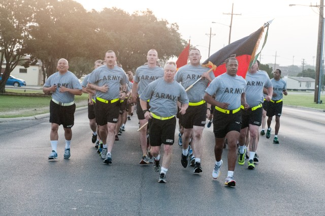 Col. Timothy Bush, center, 120th Infantry Brigade commander, alongside Command Sgt. Maj. Edward Johnson, 120th command sergeant major leads a formation of his Soldiers on Battalion Avenue in front of Division West headquarters on Fort Hood, Texas, for the division's Run to Remember, May 22. (Photo by Staff Sgt. Tony Foster, Division West Public Affairs)