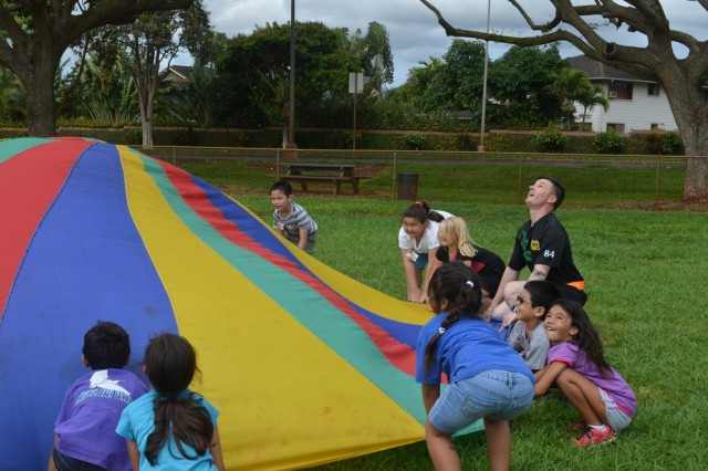 "Sgt. Kayalar Londo, a noncommissioned officer with the 26th Concrete Detachment, 84th Engineer Battalion, 130th Engineer Brigade, helps a class to launch a ball in the air with the parachute at Mililani Uka Elementary school during their ""GET FIT"" program. (U.S. Army photo by 1st Lt. Carolyn Johnson, 84th Engineer Battalion Public Affairs)"